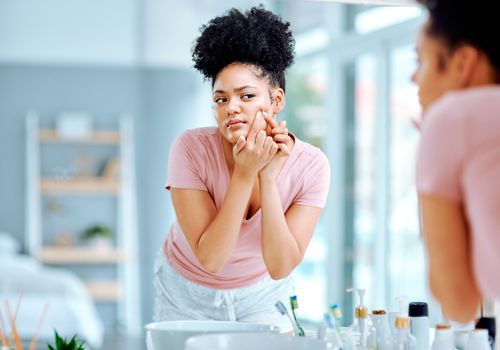 Woman examining pimple in mirror