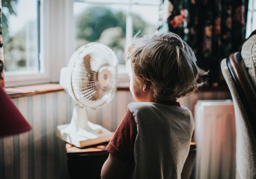 Young boy standing in front of a fan.