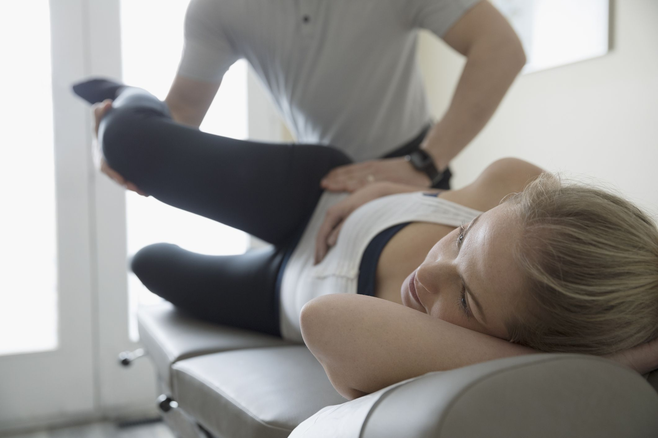 Physical therapist stretching a patient's hip.