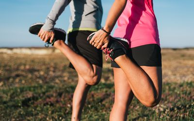 Sporty couple stretching quads before a run