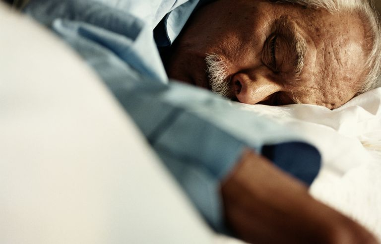 Mature man asleep on bed, close up