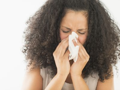 Woman sneezing, her allergy medication may dry up cervical mucus