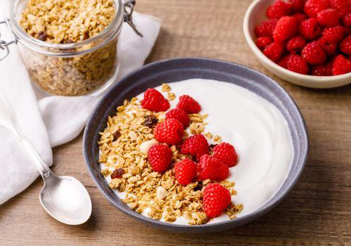 Bowl of yogurt with granola and raspberries