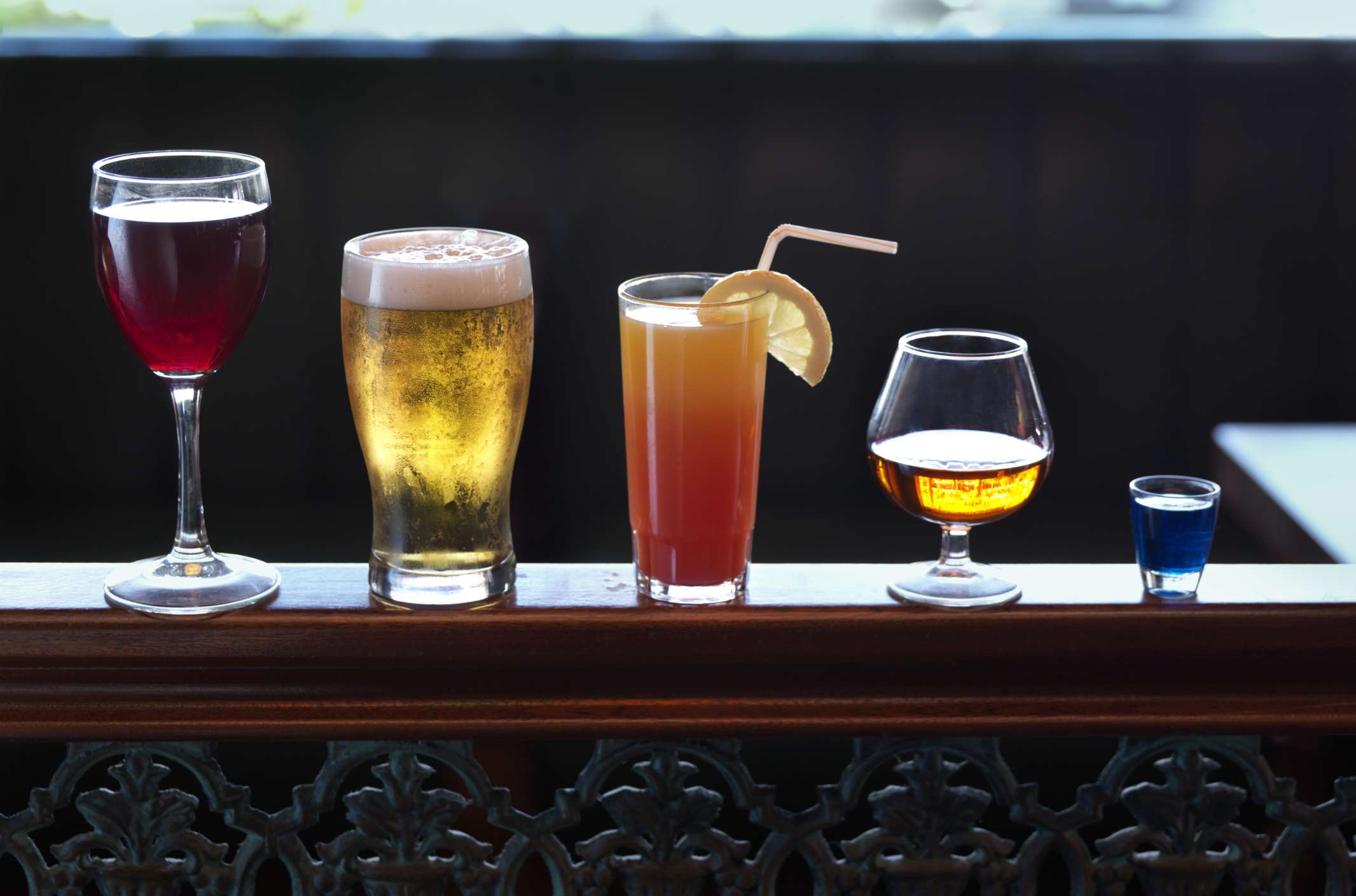 Glasses of wine, beer, a cocktail, brandy, and a shot lined up