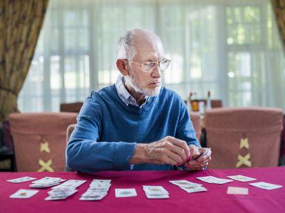 Senior man playing cards in nursing home