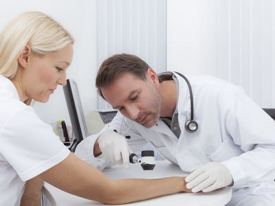 doctor doing a dermoscopy on a female patient in his office