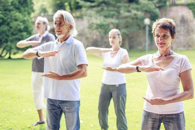 Middle age people doing tai chi outdoors