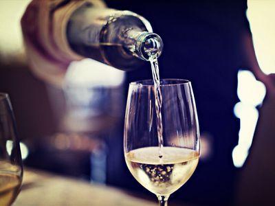 Restaurant server pouring white wine