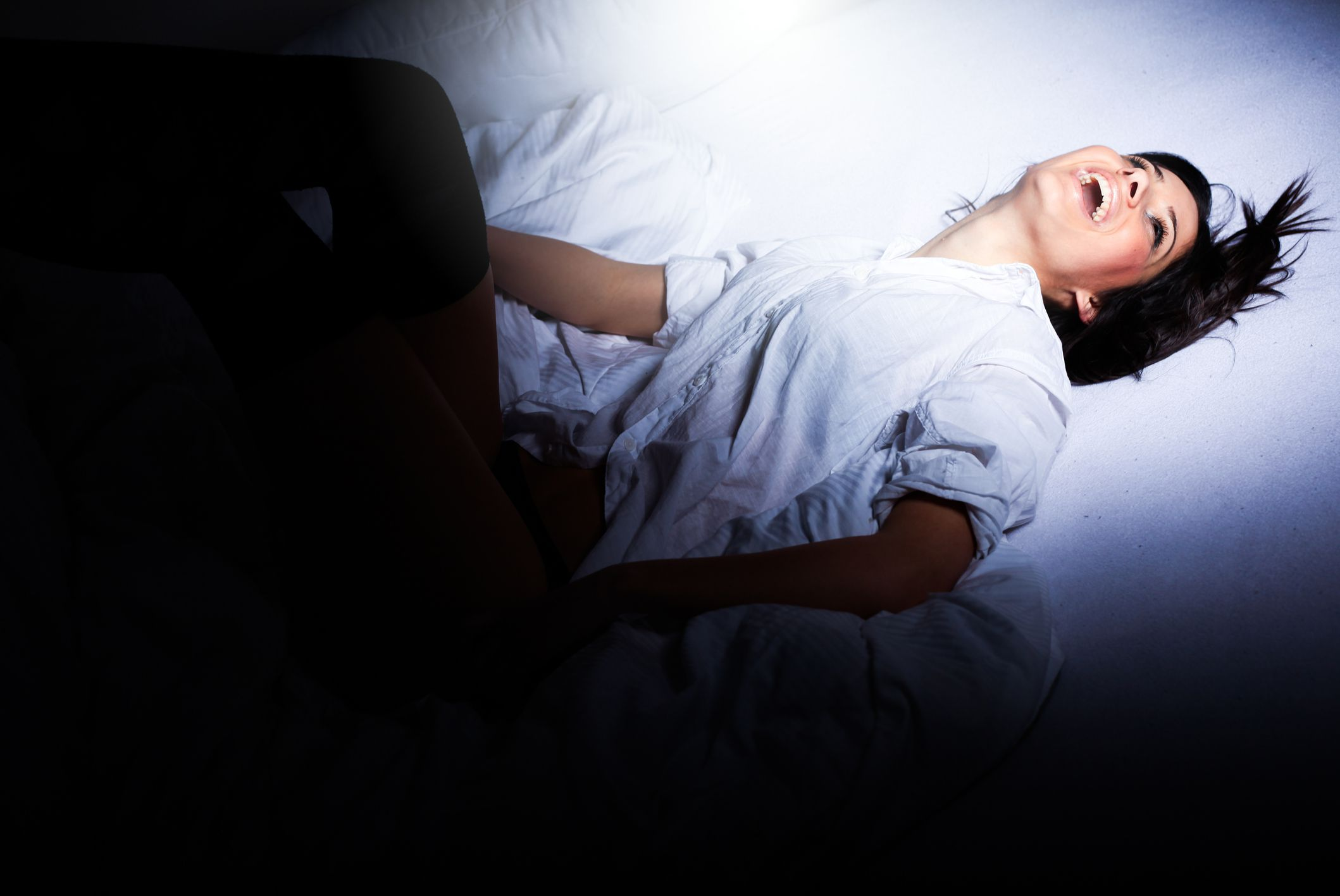 A woman lays on a bed smiling with her head back.