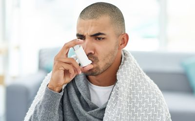 Man with cold using an inhaler