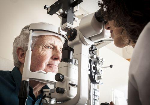 Eye doctor looking at older man's eyes