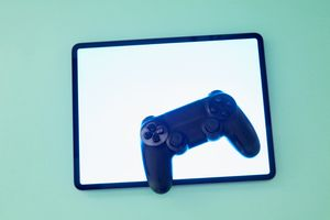 A video game controller on a lit tablet on a light blue-green background.