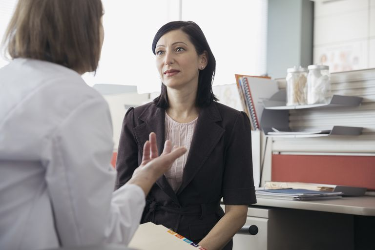 Doctor talking with patient in office Doctor talking with patient in office