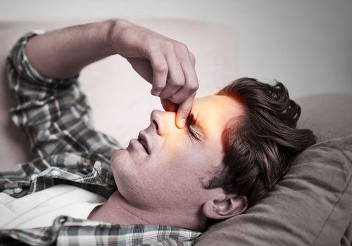 Man holding the bridge of his nose.