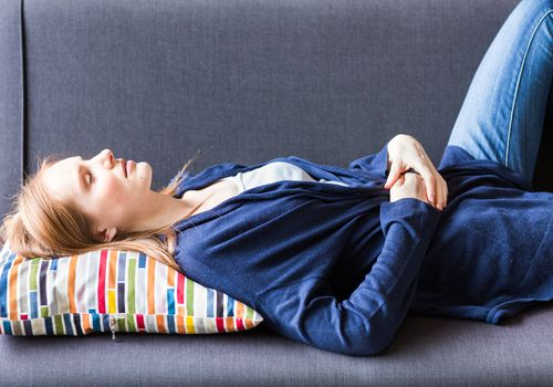 Woman lying on couch with stomach pain