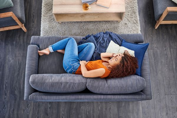 Woman lying on couch with stomach cramps