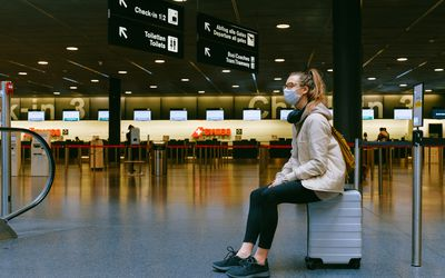 A young person wearing a mask sitting on a rolling suitcase in the middle of an empty airport terminal.
