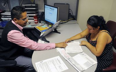 Man sitting behind a desk with a computer, helping a woman enroll in health insurance. Paperwork is on the desk between them.