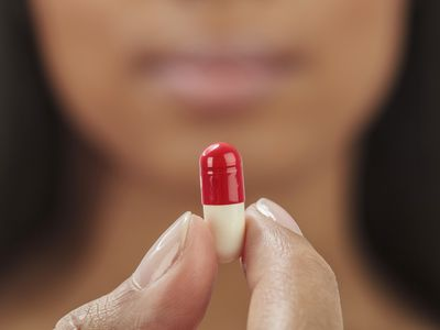 woman holding red and white pill capsule