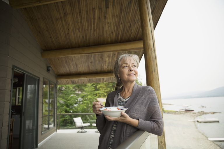 Woman eating on cabin balcony