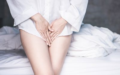 woman hand holding her crotch suffering from pain