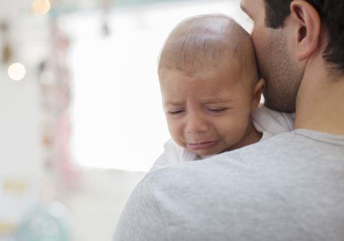 crying baby on shoulder of a man