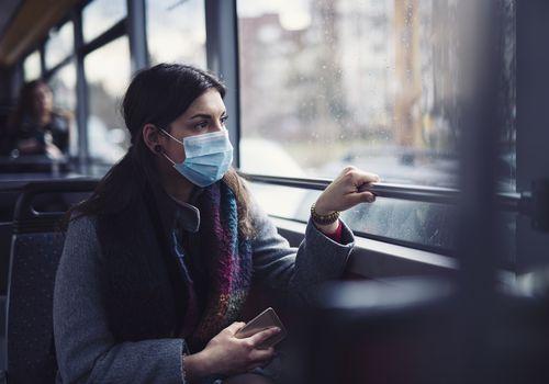 Woman looking worried on public transport wearing face mask.