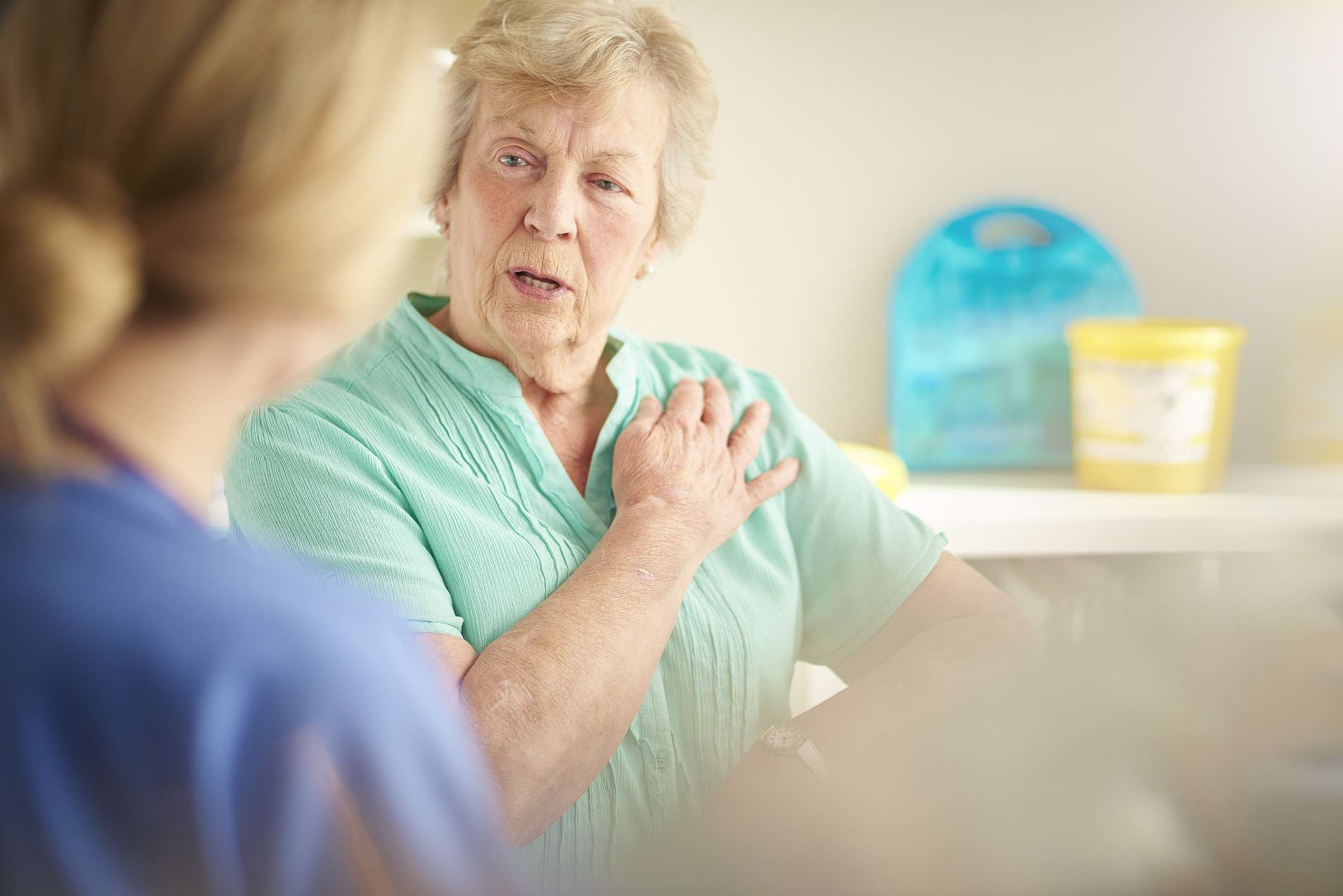 an elderly woman explaining her chest pain to her doctor
