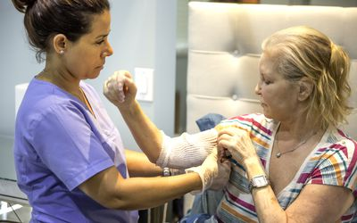 Home healthcare nurse tending to picc line of recovering patient