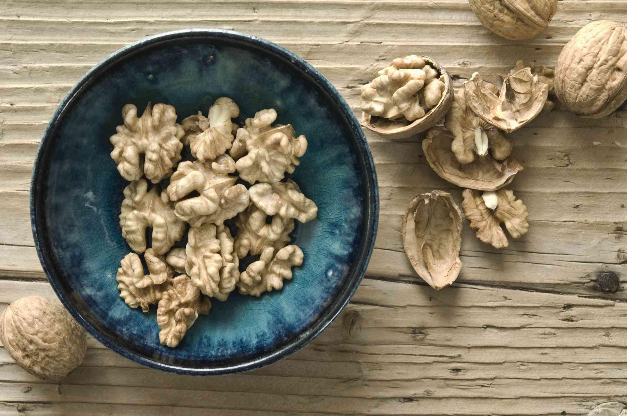 A teal bowl full of walnut halves.