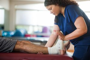 Occupational therapist holding leg and foot of patient