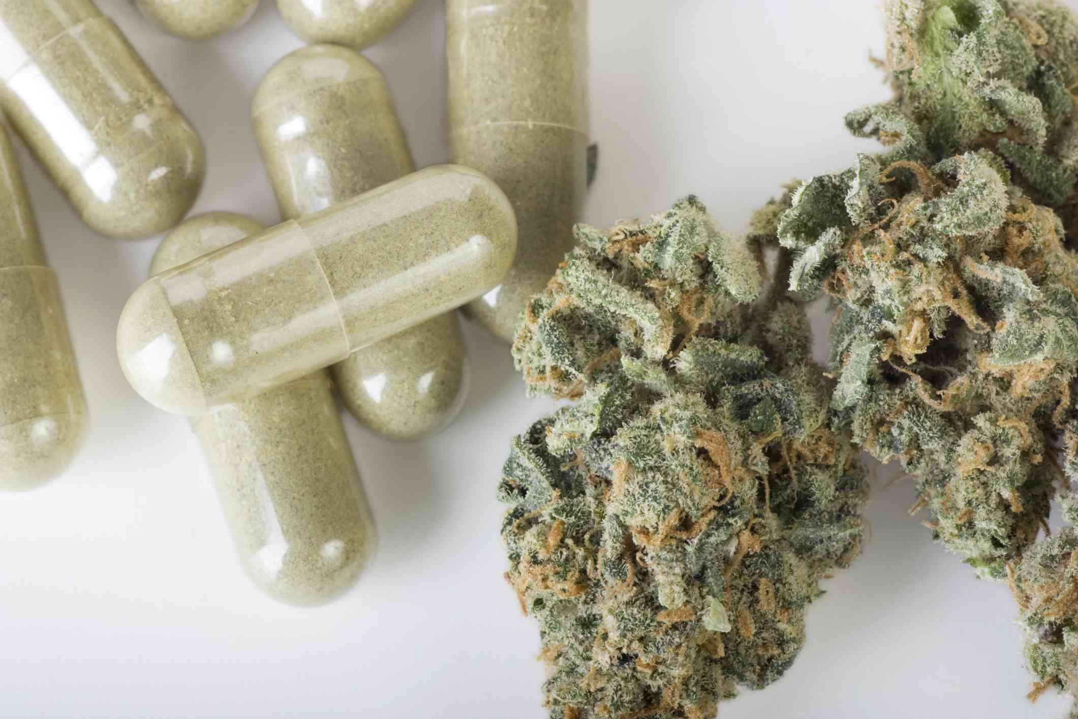 Marijuana next to pills on a white surface