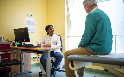 Osteopathic physician meets with older patient for primary care