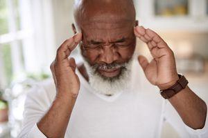 Shot of a mature man suffering from a headache at home