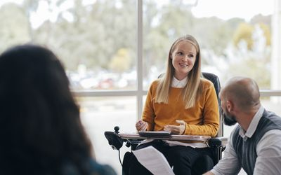 A woman looks happy and confident as she leads a group discussion at her place of work. She is a wheelchair user and has Muscular Dystrophy.