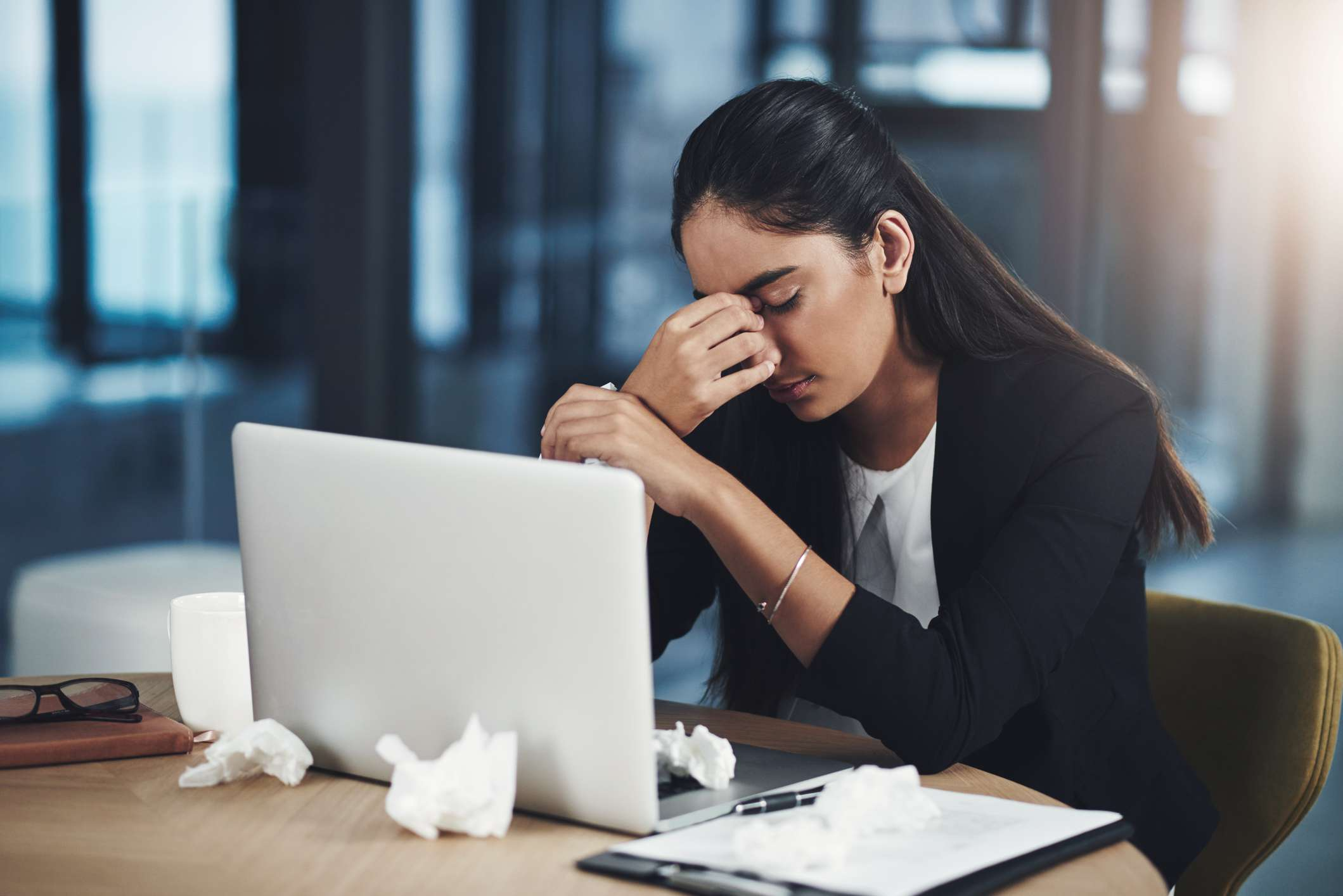 Shot of a young businesswoman suffering with a headache, holding her sinuses, while working in an office