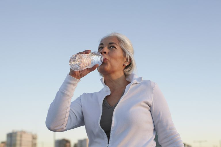 Mature woman walking while drinking water