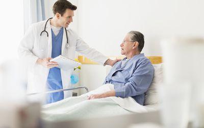 Caucasian doctor talking to Senior patient in hospital