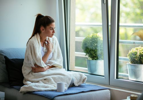 Woman with a sore throat wrapped in a blanket looking out a window