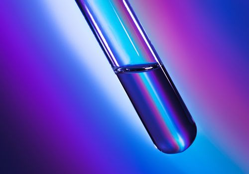 Test tube filled with clear fluid on a blue, purple, and pink gradient background.
