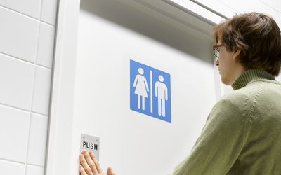 Man pushing toilet door