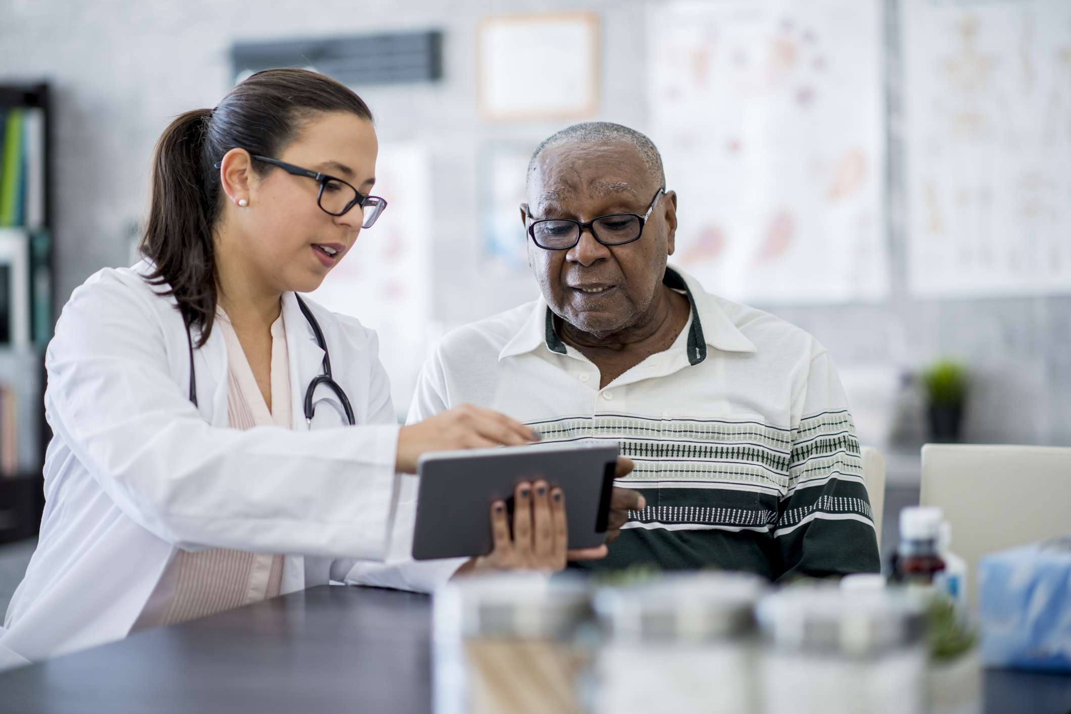 A doctor showing a patient results on a tablet