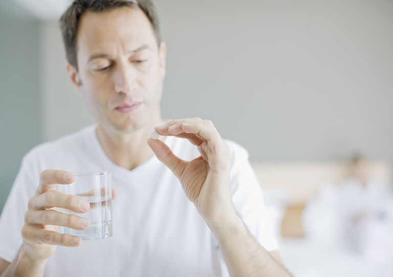 Man taking a white pill with a glass of water