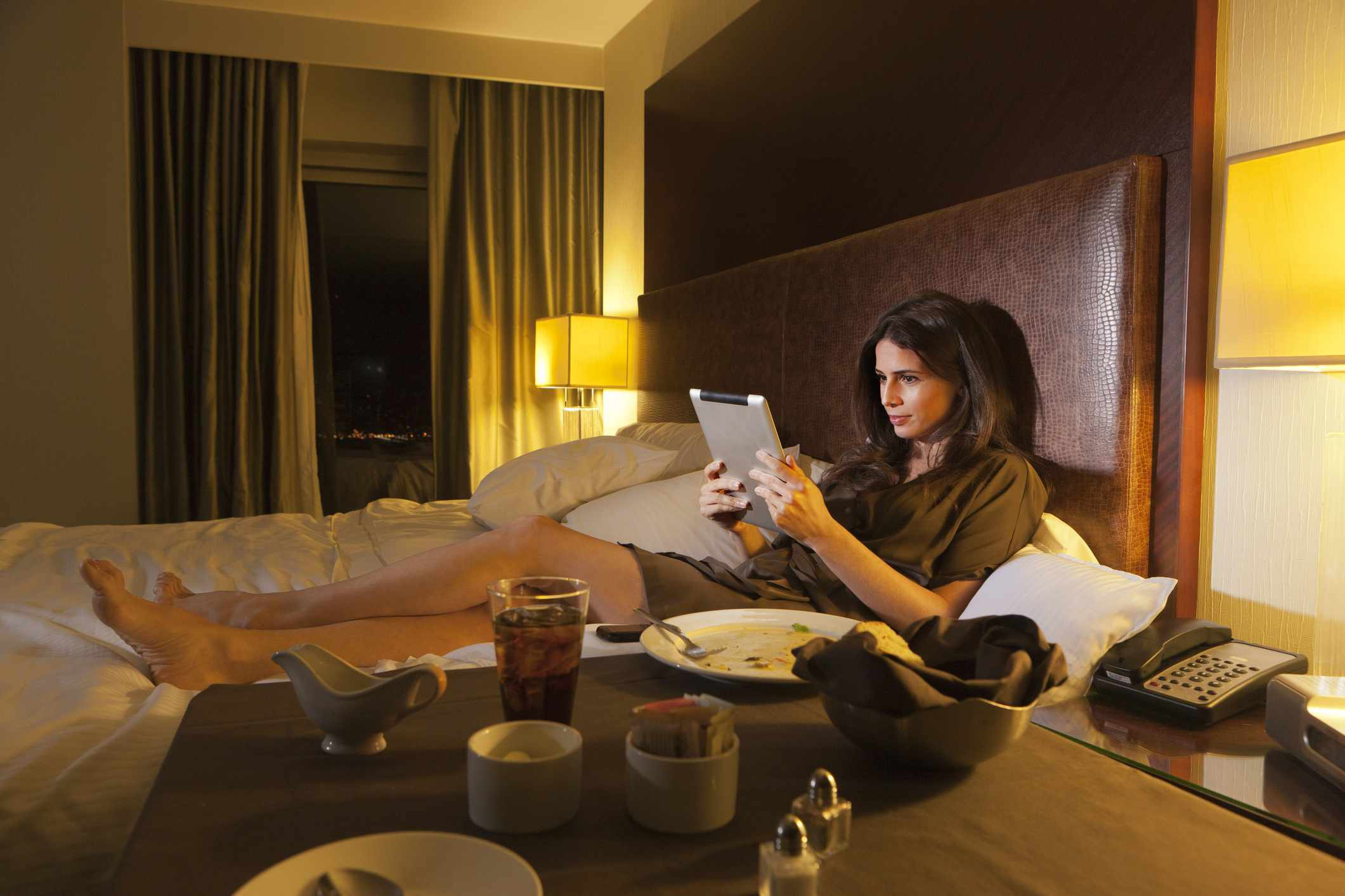 Woman reading digital tablet in bed