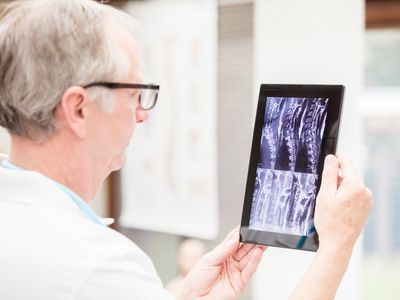 Doctor checking MRI images on tablet PC