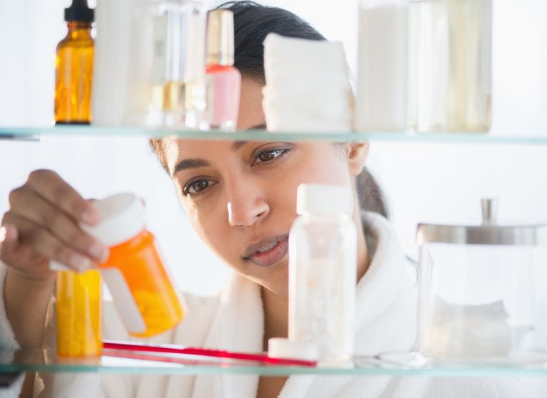 Close up of Asian woman examining label of prescription bottle