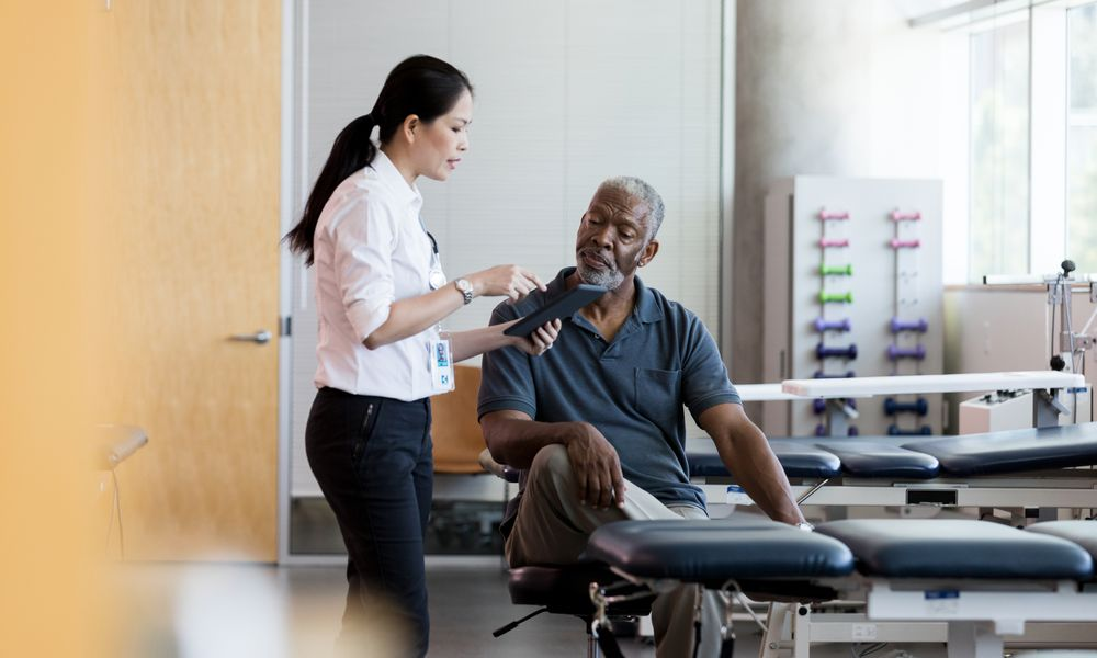 A female PT talks with a male older patient.