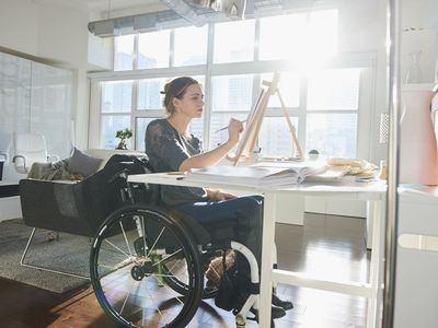 A woman in a wheelchair painting on an easel
