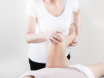 Physical therapist manipulating patient's leg
