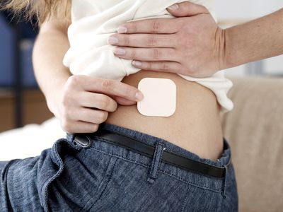 Person placing a (generic) contraceptive patch on their lower back.